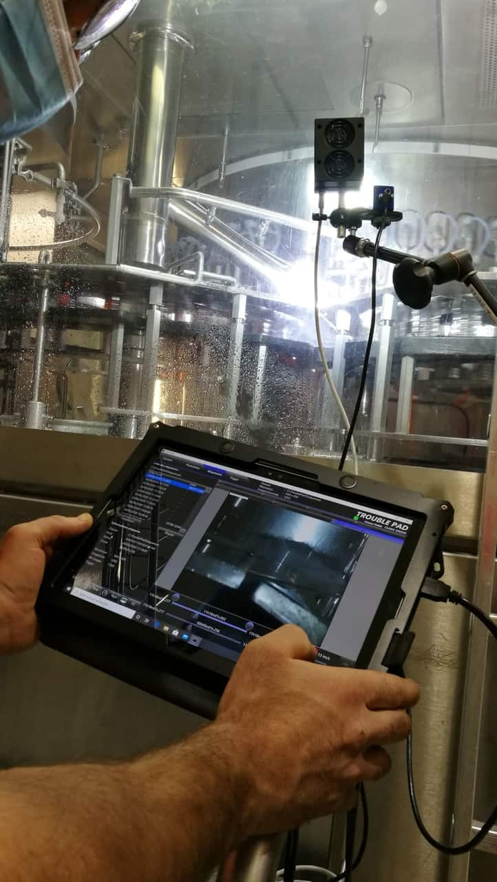 A maintenance operator setting up the TroublePad high-speed camera on a high-speed bottling line.